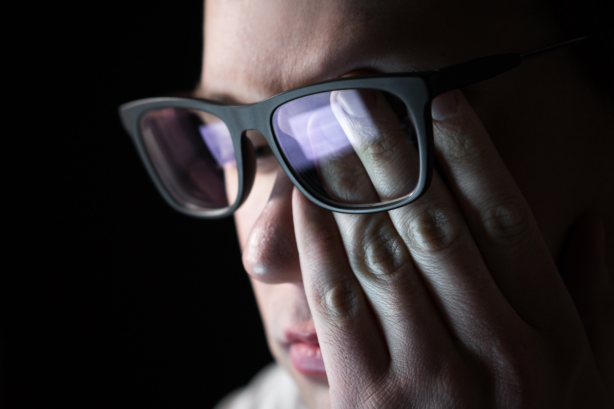 Man rubbing tired eyes. Problem with glasses, eyesight or vision. Person having stress or depression. Workplace bullying. Working late with computer. Astigmatism, myopia or insomnia. Dramatic mood.